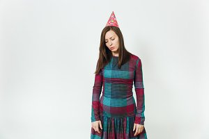 Beautiful caucasian young sad distressed woman in plaid dress and birthday party hat with long brown hair, celebrating holiday without gift on white background isolated for advertisement.
