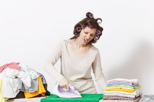 Distressed housewife with curlers on hair in light clothes ironing family clothing on ironing board with iron. Woman isolated on white background. Housekeeping concept. Copy space for advertisement.