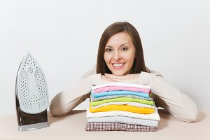 Close up fun tired shocked housewife in light clothes ironing checkered shirt, clothing on ironing board with iron. Woman isolated on white background. Housekeeping concept. Copy space advertisement.