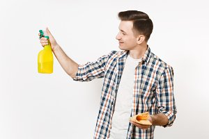Young housekeeper man holding cleaning rag, white blank empty spray bottle with cleaner liquid isolated on white background. Male doing house chores. Copy space for advertisement. Cleanliness concept.