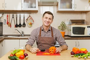 Handsome smiling caucasian young man in an apron, brown shirt sitting at table, cuts vegetable for salad with knife in light kitchen. Dieting concept. Healthy lifestyle. Cooking at home. Prepare food.