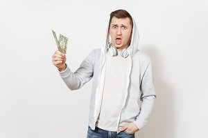 Young handsome student in t-shirt, blue jeans and light sweatshirt with hood with headphones holds two one-dollar bills and surprised looks in studio on white background. Concept of emotions