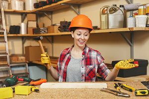 Pretty caucasian young brown-hair woman in plaid shirt, gray T-shirt, yellow gloves, protective helmet working in carpentry workshop at wooden table place with hammer, piece of wood, different tools.