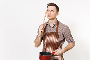 Young pensive man chef or waiter in striped brown apron, shirt holding red empty stewpan, wooden spoon isolated on white background. Male housekeeper or houseworker. Kitchenware and cuisine concept.