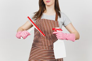 Close up cropped portrait housewife in pink gloves, striped brown apron isolated on white background. Woman holding squeegee, spray bottle with cleaner liquid for cleanup. Copy space for advertisement