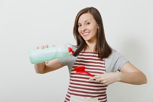 Young housewife in striped apron isolated on white background. Beautiful housekeeper woman holds bottle with cleaner liquid, pours on brush for washing dishes. Bottle with copy space for advertisement