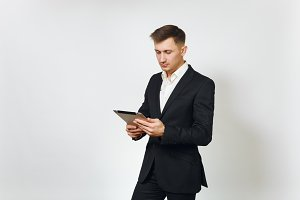 Young successful handsome rich business man in black suit working on modern tablet isolated on white background for advertising. Concept of money, achievement, career and wealth in 25-30 years.