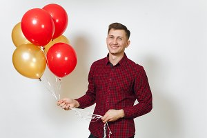Handsome caucasian smiling fun young happy man 25-30 years in red plaid shirt with yellow golden balloons, celebrating birthday, on white background isolated for advertisement. Holiday, party concept.