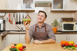 Handsome smiling European young man in apron, brown shirt sitting at table with vegetable salad in bowl in light modern kitchen. Dieting concept. Healthy lifestyle. Cooking at home. Prepare food.