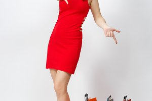 Full length glamour caucasian young brown-hair woman in red dress pointing fingers down, holding multicolored packets with purchases shopping isolated on white background. Copy space for advertisement