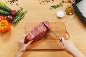 Raw meat. Fresh beef tenderloin on cutting board on wooden table with different vegetables, spices, mushrooms, baking tray, knife. Top view flat lay Copy space for advertisement. Woman cuts with knife