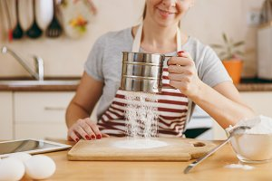 A young smiling woman sifts flour with an iron sieve with tablet on the table in the kitchen. Cooking home. Prepare food.