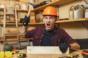 Crazy aggressive angry caucasian young man in plaid shirt, black T-shirt, orange protective helmet, gloves working in carpentry workshop at wooden table place with piece of wood hammer different tools