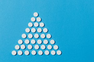 Medication white round tablets arranged in form of triangle isolated on blue color background. Pills geometric pyramid shape. Concept of health, treatment, choice, lifestyle. Copy space advertisement.