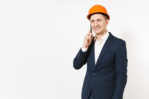 Young handsome smiling businessman in dark suit, protective construction orange helmet talking on mobile phone isolated on white background. Male worker for advertisement. Business, working concept.