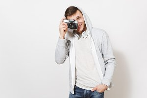 Young handsome smiling man student in t-shirt, light sweatshirt with hood with headphones takes pictures on retro camera and holds hand in pocket isolated on white background. Concept of photography