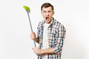 Young combative angry housekeeper man in checkered shirt holding and sweeping with green broom isolated on white background. Male doing house chores. Copy space for advertisement. Cleanliness concept.