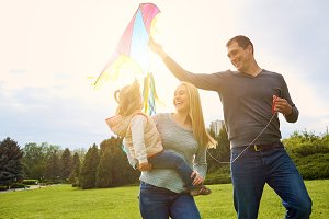 Happy family with colorful kite on nature. Sunlight.