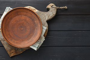 Clay plate on rustic cutting board