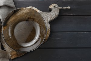 Empty glass plate on rustic cutting