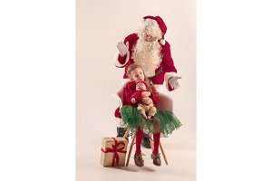 Christmas portrait of cute little newborn baby girl, dressed in christmas clothes, studio shot, winter time
