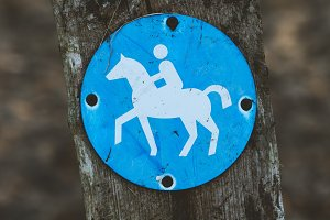 Bridle path round blue sign on a wooden stake, with blurry land path in the background. Germany