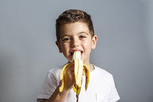 Cute little boy eating banana