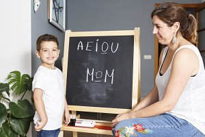 Litlle kid writing the word Mom