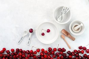 Cherries and white porcelain baking dishes with measuring spoons on a white stone background. Minimalist cherry pie baking concept.