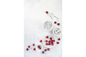 Minimalist cooking concept with red cherries and porcelain baking dishes on a white stone background. White on white flat lay with copy space.