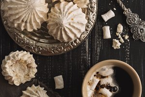 Meringue and coffee with marshmallow on a dark rustic background. The view from above, flat lay.