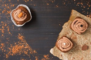 Cupcakes with chocolate cream are decorated on a dark rustic background. Top view, copy space.