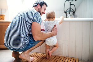 Father with a toddler child at home standing by the tub in the bathroom.