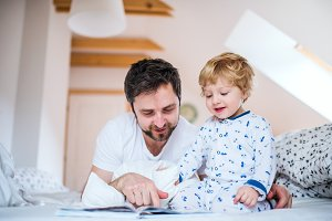 Father with toddler boy reading a book on bed at home at bedtime.