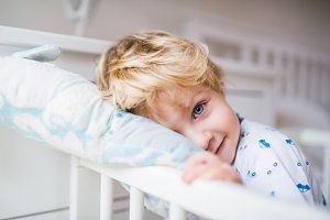 A toddler boy standing in a cot in the bedroom at home.