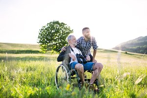 An adult hipster son with senior father in wheelchair on a walk in nature at sunset.