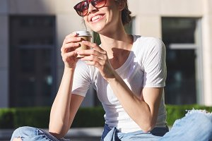 a young smiling woman in casual clothes sit outdoors with paper cups of coffee in her hands