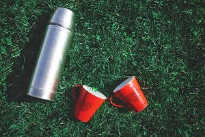 a metal thermos and two red mugs on the grass