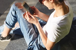 a woman sits on the street with a phone in hands