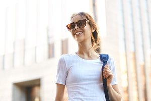 portrait of a young attractive woman walking city at sunny day