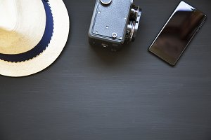 Vintage camera, hat and smartphone