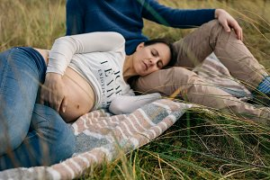 Pregnant sleeping on a blanket on the grass