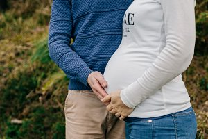 Pregnant with partner holding belly