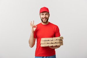 Delivery Concept: Handsome pizza delivery man making OK sign isolated over grey background.