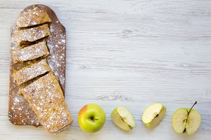 Strudel or apple pie on wooden board