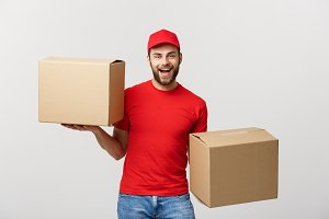 Portrait delivery man in cap with red t-shirt working as courier or dealer holding two empty cardboard boxes. Receiving package. Copy space for advertisement