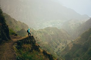 Hiker with backpack on the mountain top. Rocky terrain of a incredible panorama view of high mountain ranges and deep ravines around. Santo Antao Cape Verde