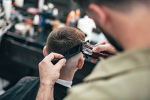 Men's haircut in barbershop. Hair Care. Barber cuts the client.