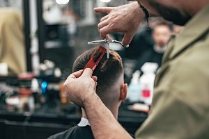 Confident guy sitting at beauty salon . Man haircut. Soft focus.