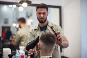 Men's haircut in barbershop. Hair Care. Barrer makes hair styling.